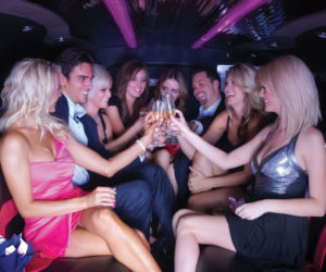 Girls having drink in the limo and pink light glowing.