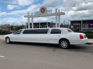 White limousine parking by R sign.