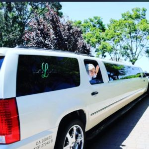 White color Bride Wedding Limo taking hand when limo was leaving