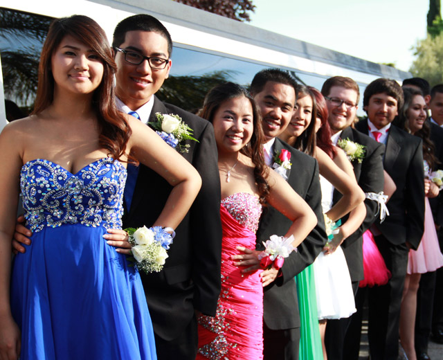Prom girls was standing by limo and taking pictures.
