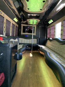 Turlock Limo party bus interior with green glowing light and wrap around seat.